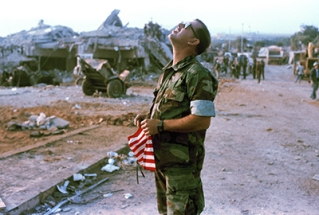 An unidentified Marine holds a flag and stares skyward at the U.S. Marine base after a massive bomb blast that destroyed the base and caused a huge death toll rising to 239, near Beirut airport, Oct. 23, 1983. The number of dead included 218 Marines, 18 Navy men and 3 Army personnel. (AP Photo/Mark Foley)